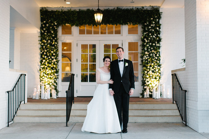 Ellison and Cullen standing in front of the first door decor at the Cape Fear Country Club