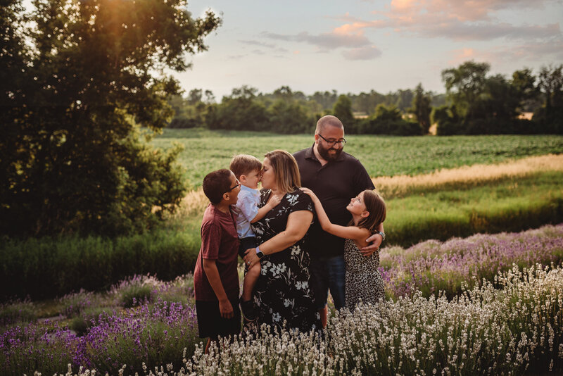 Family of five embracing in a lavender field at sunset