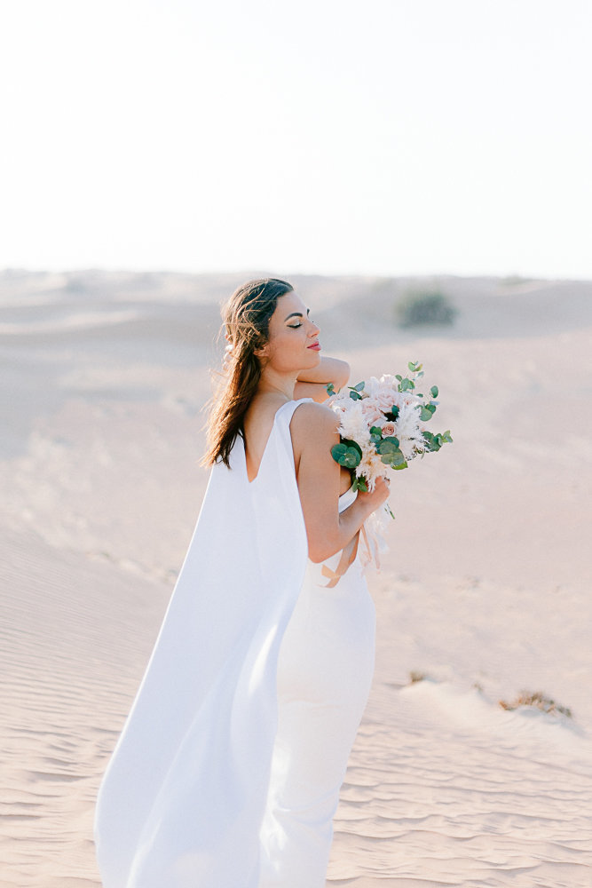 bride looking at the sky with a bouquet in lahbab desert in duabi amirat Arab United