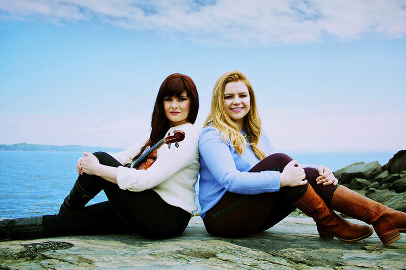 Music Duo photo Cassie and Maggie sitting on rocks knees bent ocean behind them