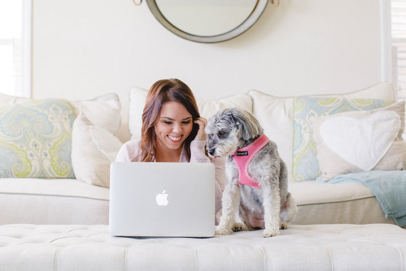 Emily Yost working on her laptop with her dog