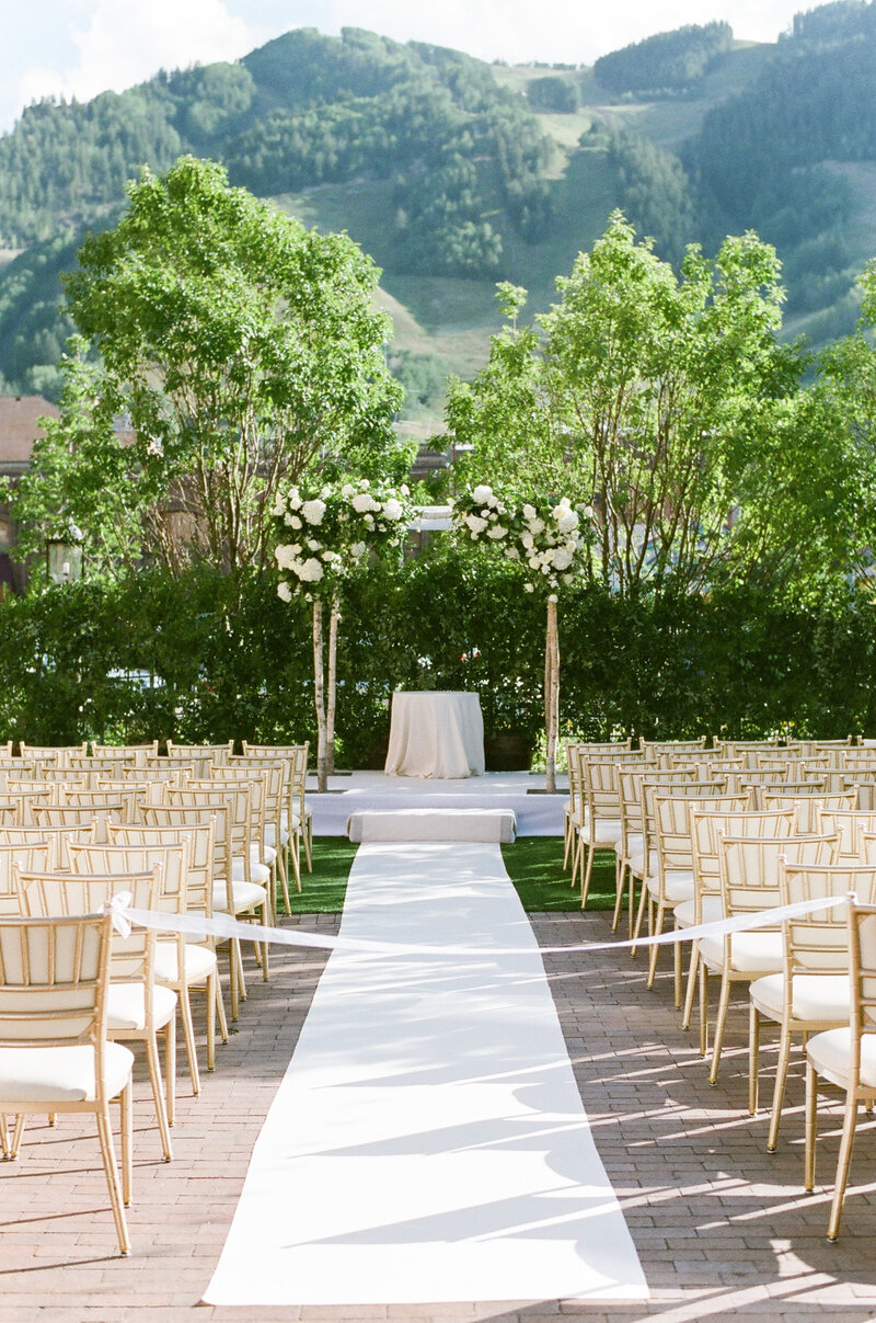 Empty outdoor wedding aisle with white runner, gold chairs, and flower-covered chuppah