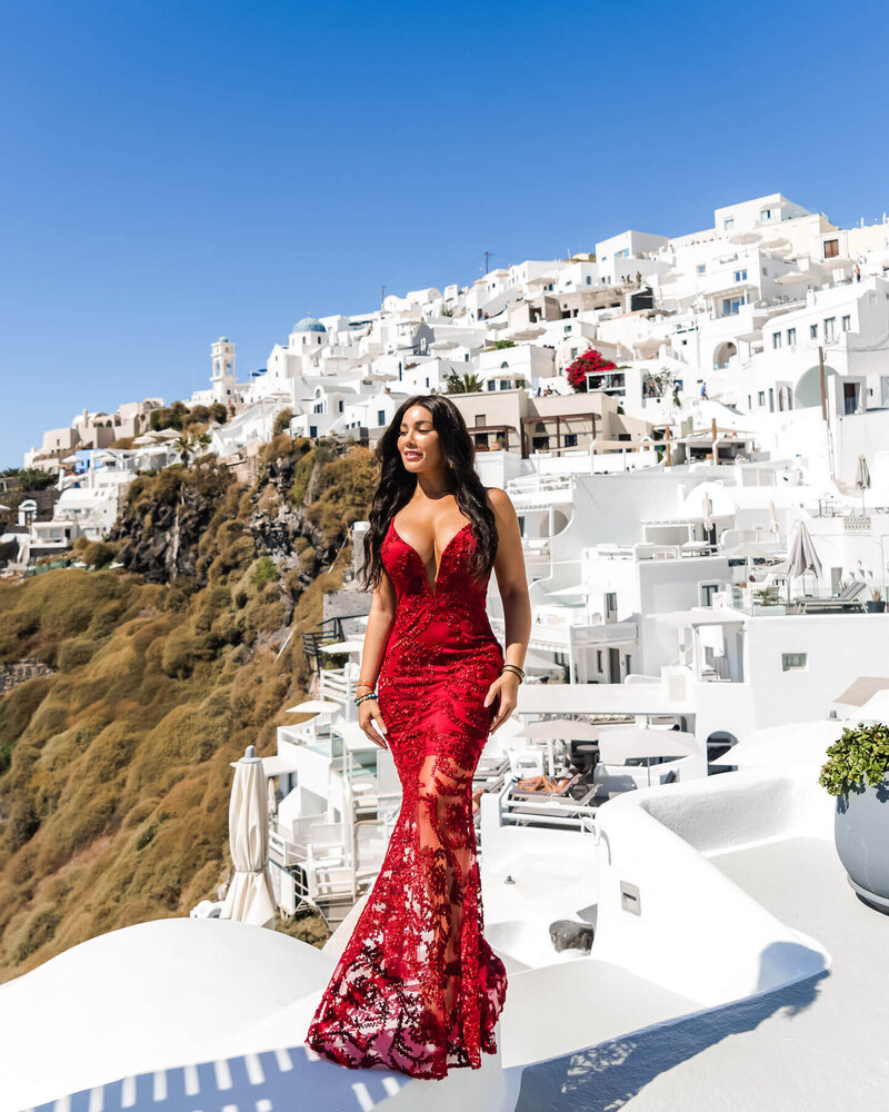 luxury travel blogger and digital content creator - Isabella standing in red dress in Greece