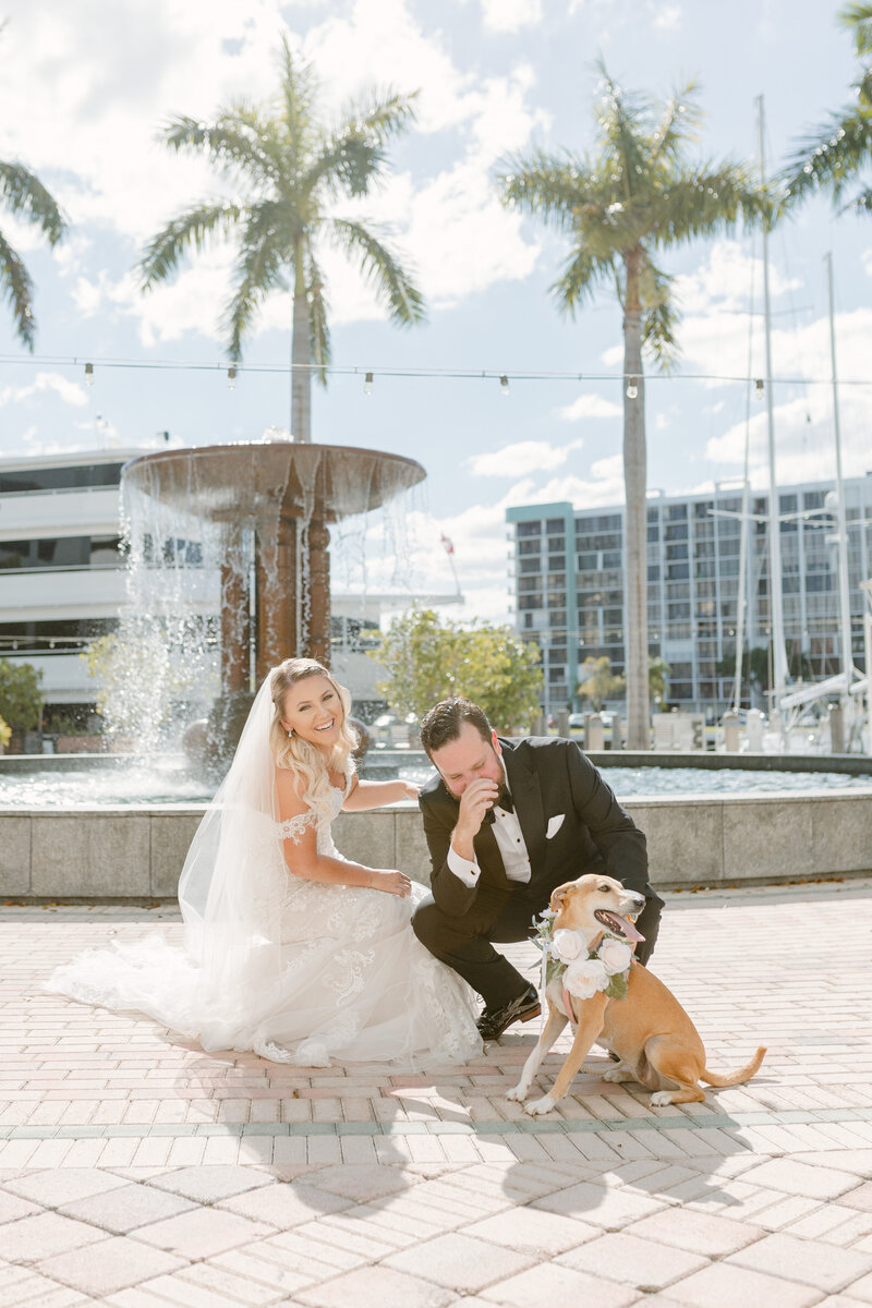 Bride and groom laugh on their wedding day with their dog