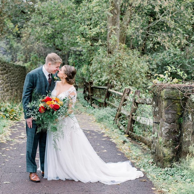 Bride and Groom are smiling at each other just after their wedding. The couple is outdoors surrounded by greenery. The bride is holding a colorful floral bouquet. There is a rustic wood fence and stone wall next to them.