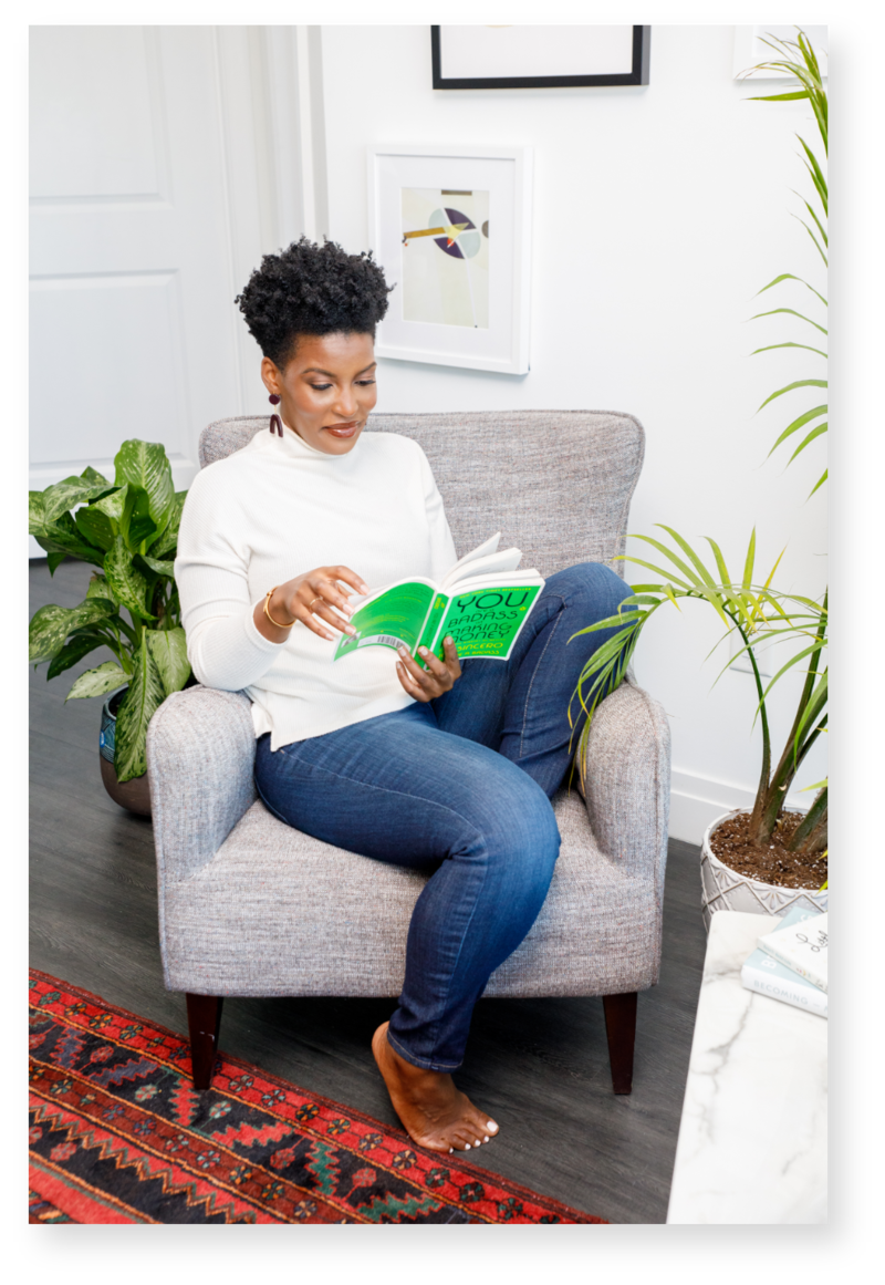 Woman with short and curly hair reading while sitting down on a gray chari