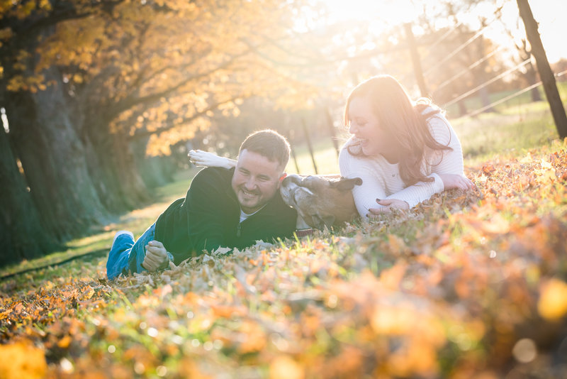 Couple and thier dog having fun during fall engagement session at the Penny Psrk philadelphia PA
