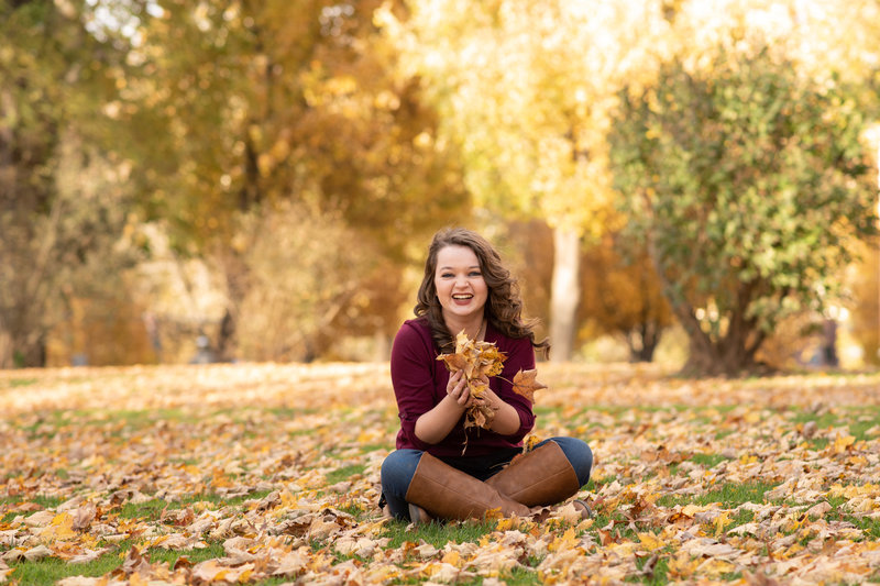 Senior girl sitting on ground throwing golden leaves