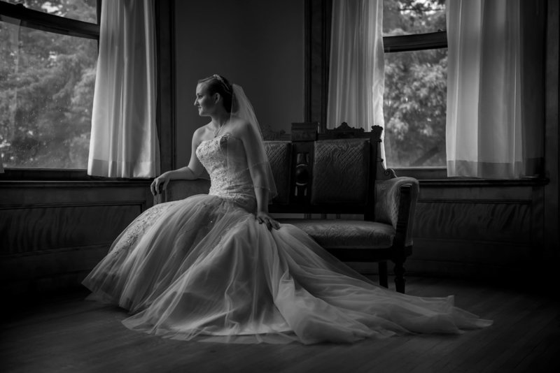 bride sitting by window at Joslyn Castle in Omaha Nebraska