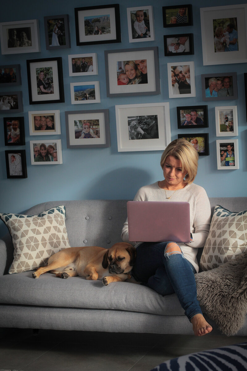 Wendy Griffith working on her laptop with family photos on the wall behind her