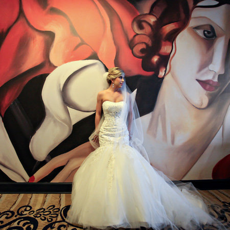 Pretty wedding with bride leaning up against a painting. Wedding was in the sawyer room and review  happy review  for photographers