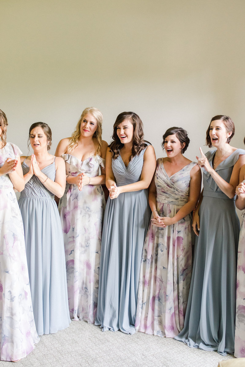A group of bridesmaids smile and tear up as they see the bride in her dress for the first time on the wedding day