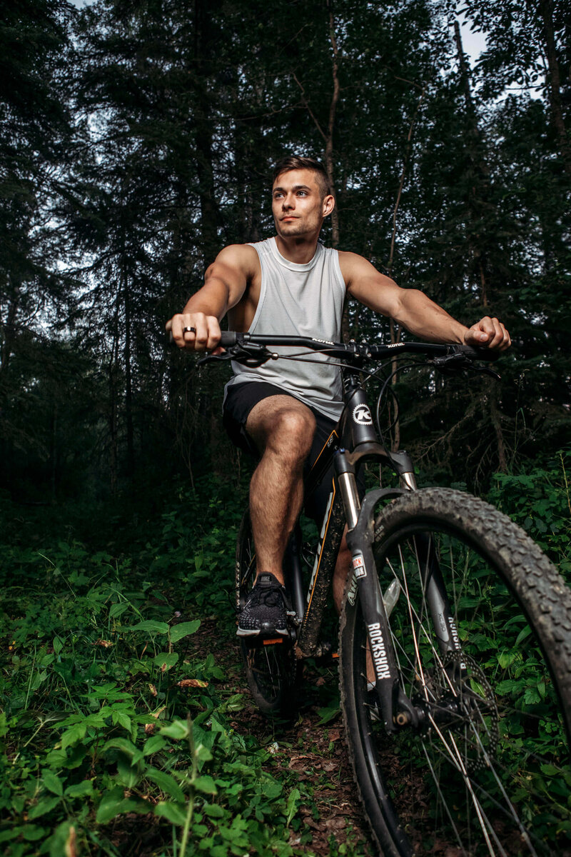 muscular man on mountain bike in forest