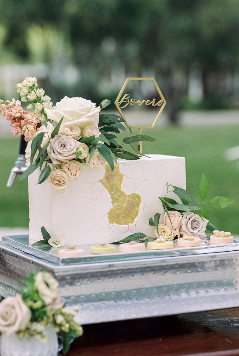 Picture of wedding details on film. Modern cake, gold crack in cake with florals, colors, dusty pink, greenery, white roses, gold cake topper,  wedding photography in orange county