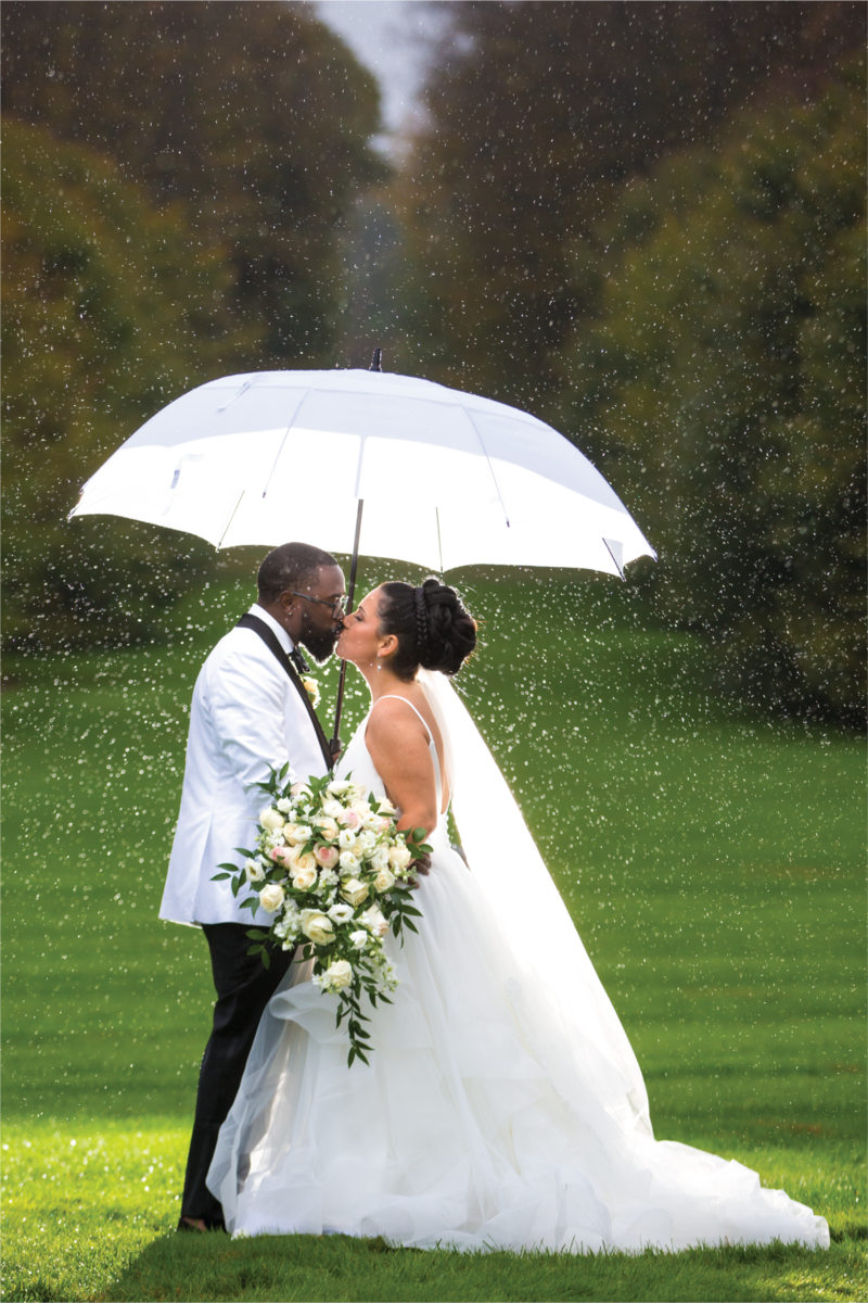 david_perlman-weddingCoupleUnderUmbrellaKissing