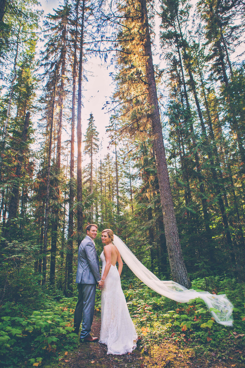 bride and groom waling in forest with veil blowing