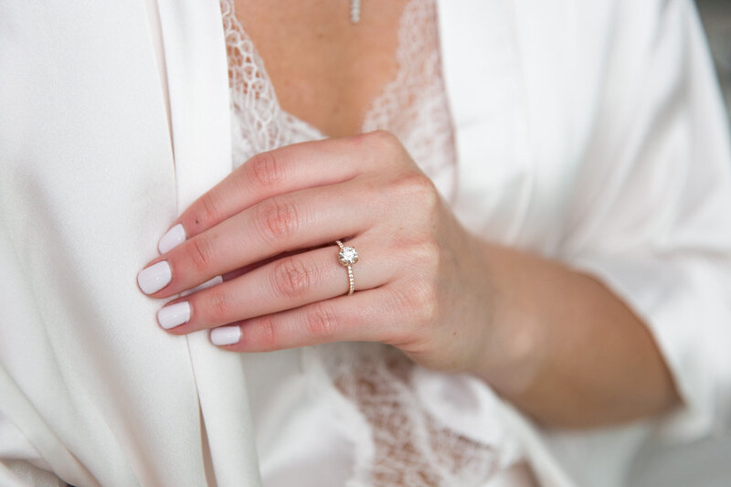 bride's hand on white robe with ring