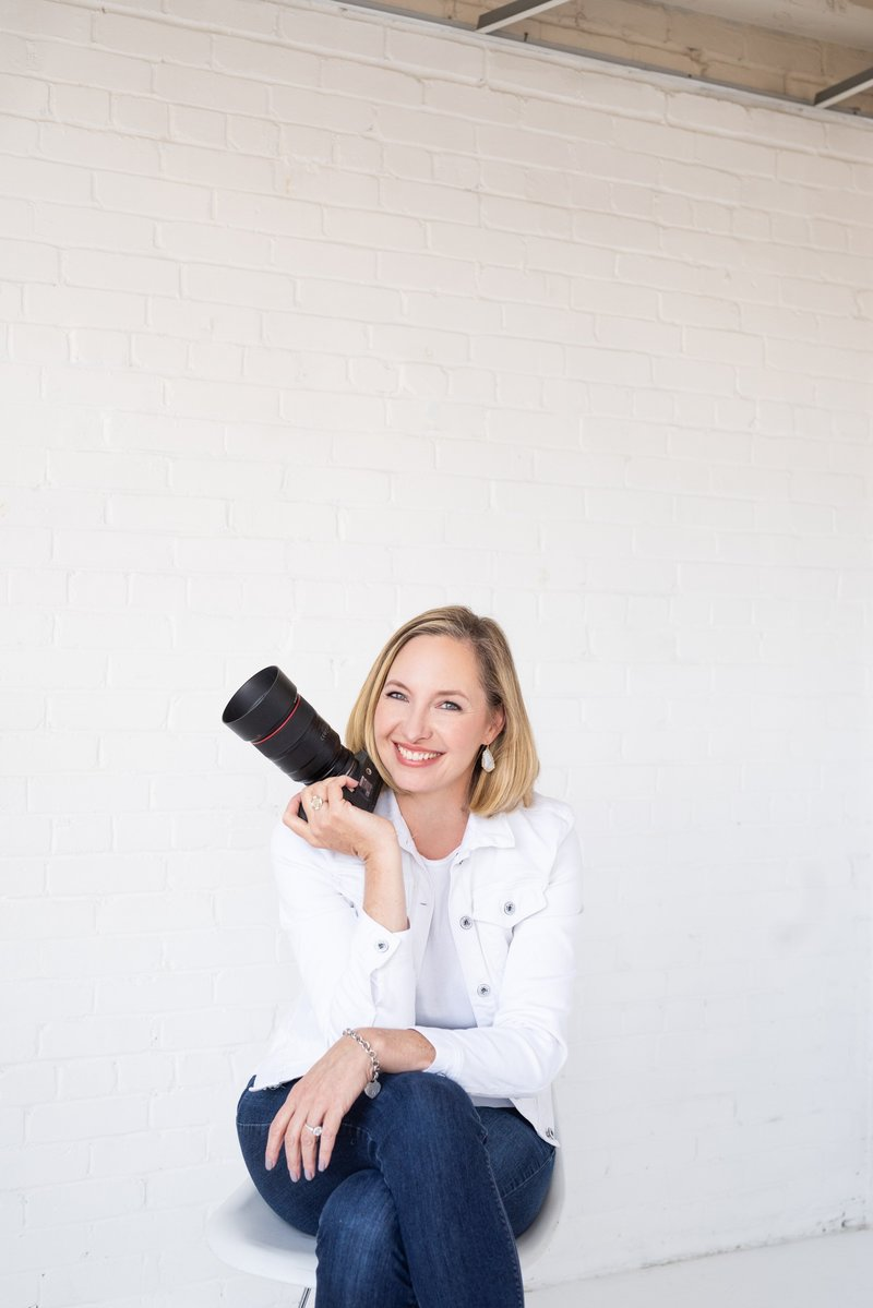 Jennifer Denton holding a camera sitting down in front of white wall