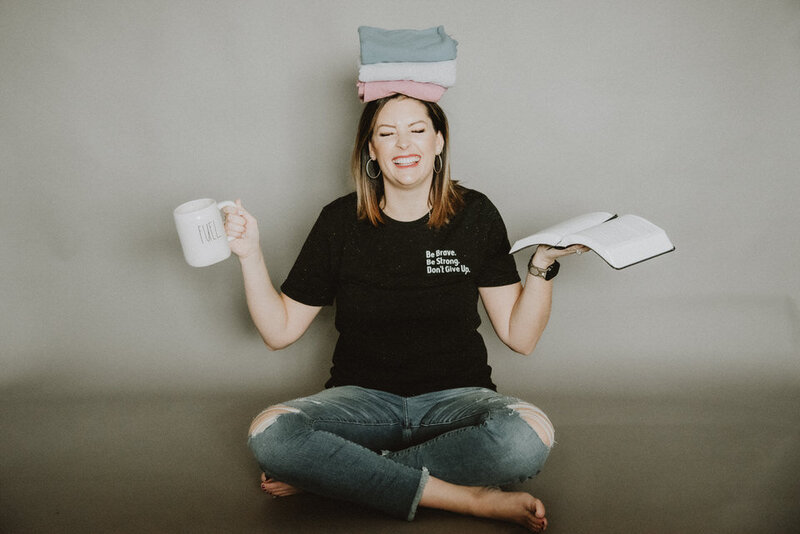 woman smiling holding coffee cup, notebooks, and t-shirts