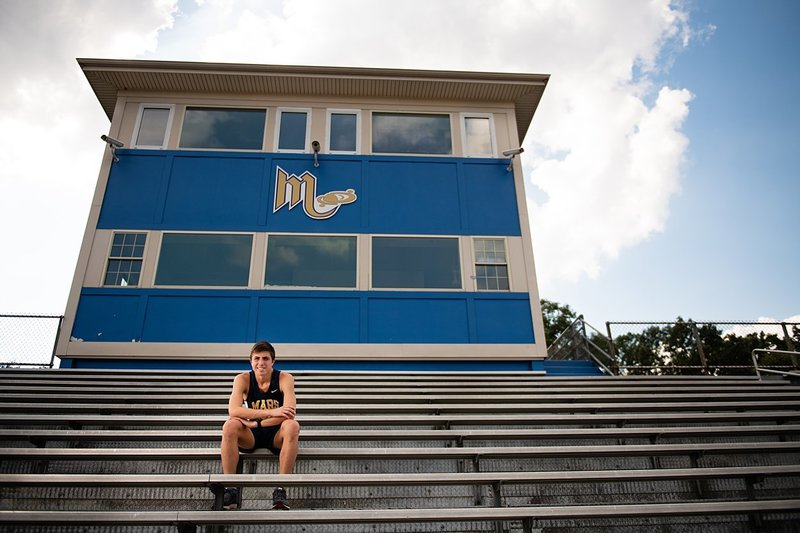 High school senior boy wearing track uniform seated in bleachers at Mars High School stadium in Pittsburgh, PA