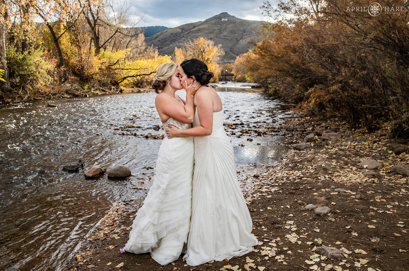 Brides kiss on their wedding day with Clear Creek in the backdrop in Golden Colorado