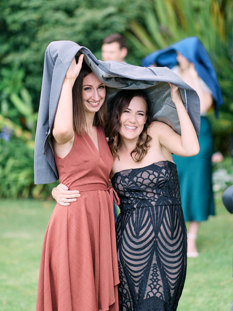 Two wedding guests hide underneath jacket to stay out of the rain