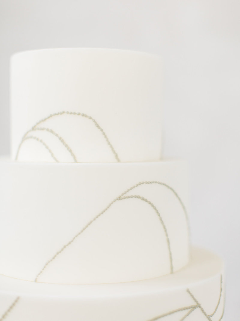 This all white and grey wedding cake is a modern minimal take on a classic with orchid inspired design