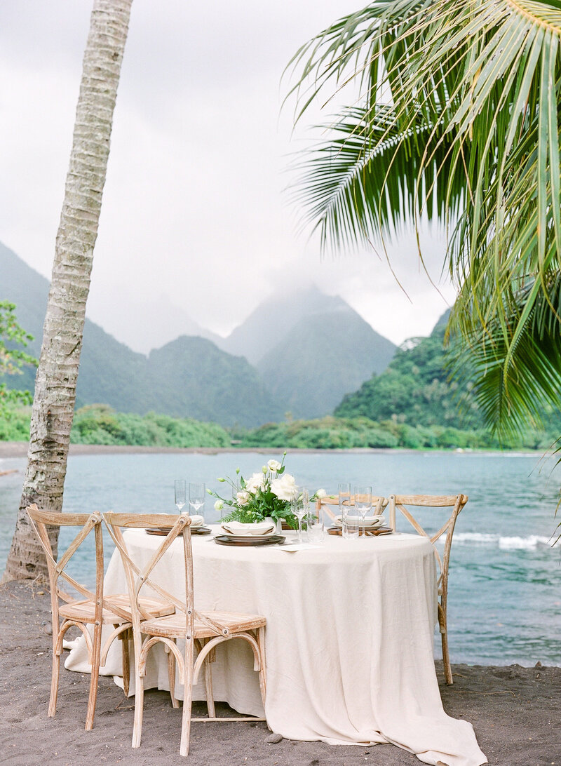 Table design with view on the moutain on the black sand beach, fine art wedding style in Tahiti