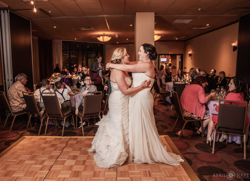 Two brides dance in the small ballroom Golden Vista at The Golden Hotel