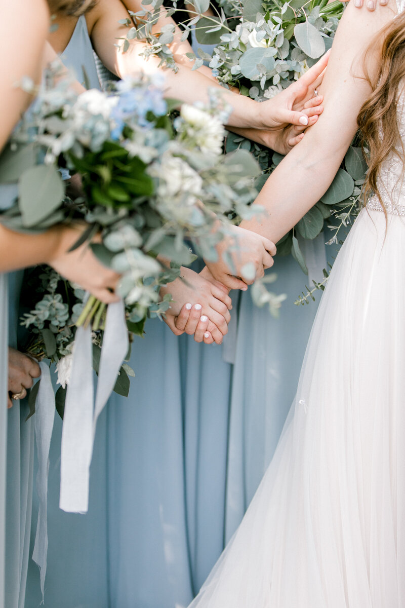 bridesmaids hold bride's hand