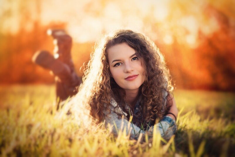 teen girl lays on her stomach in a field and smiles for senior portrait photograph