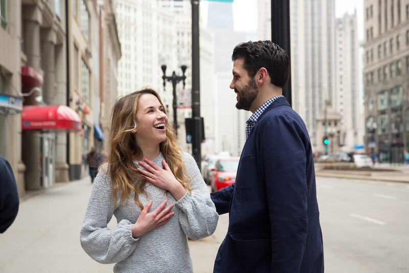 couple laughing after surprise proposal woman gasping from surprise engagement downtown chicago mag mile