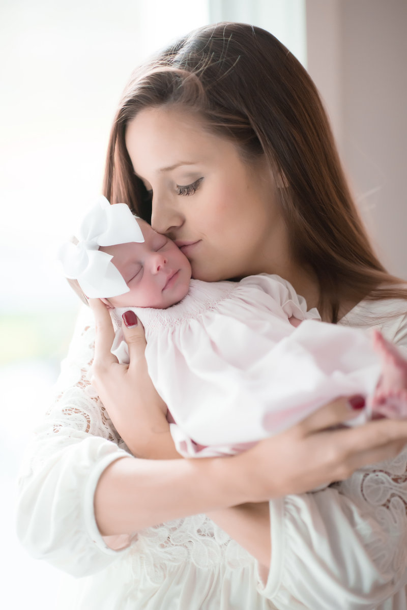 mother in white top kissing baby girl