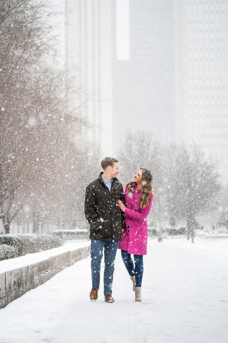 fiance walks snowy winter engagement session in Millennium Park Chicago