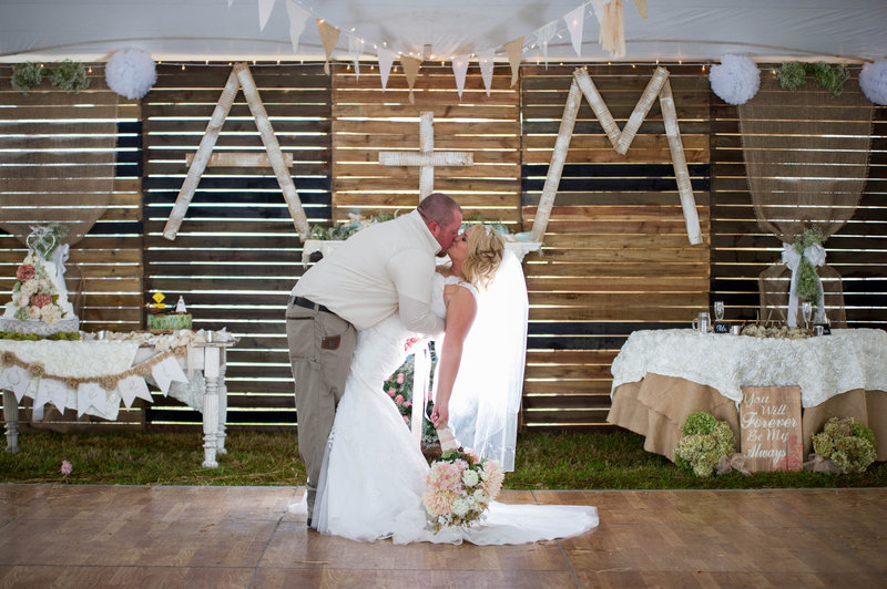 bride and groom kiss in front of DIY pallet wall