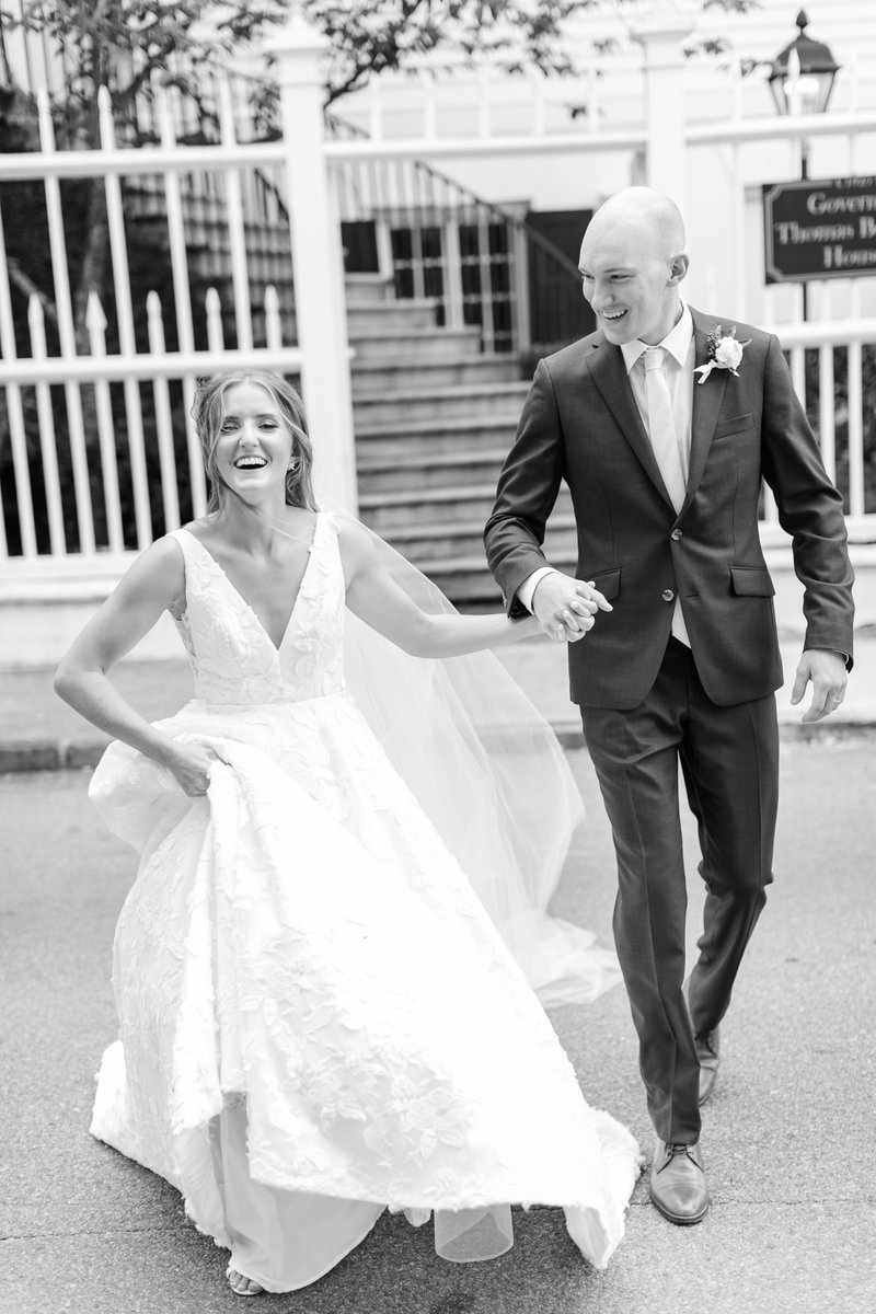 Bride and groom running through the street on their wedding day at Governor Thomas Bennett House in Charleston South Carolina