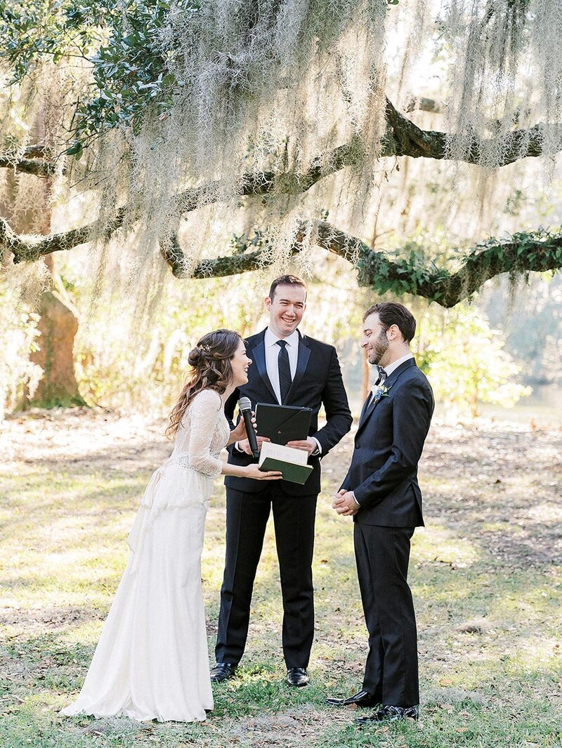 Bride in wedding dress and groom in suit being married by a celebrant under a tree in South Carolina