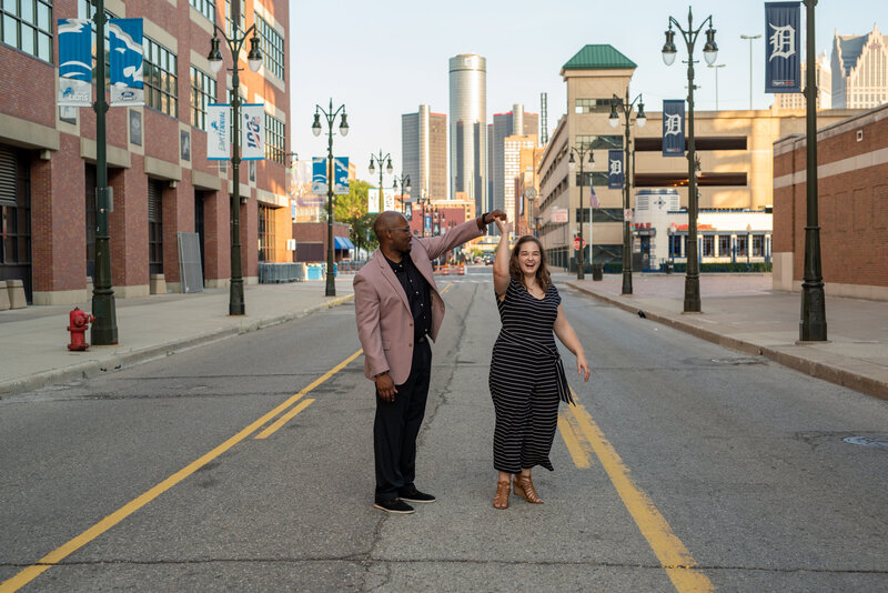 Couple dancing in the street during engagement photos.