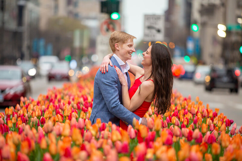 A creative magnificent mile engagement photo with tulips on Michigan ave in Chicago.