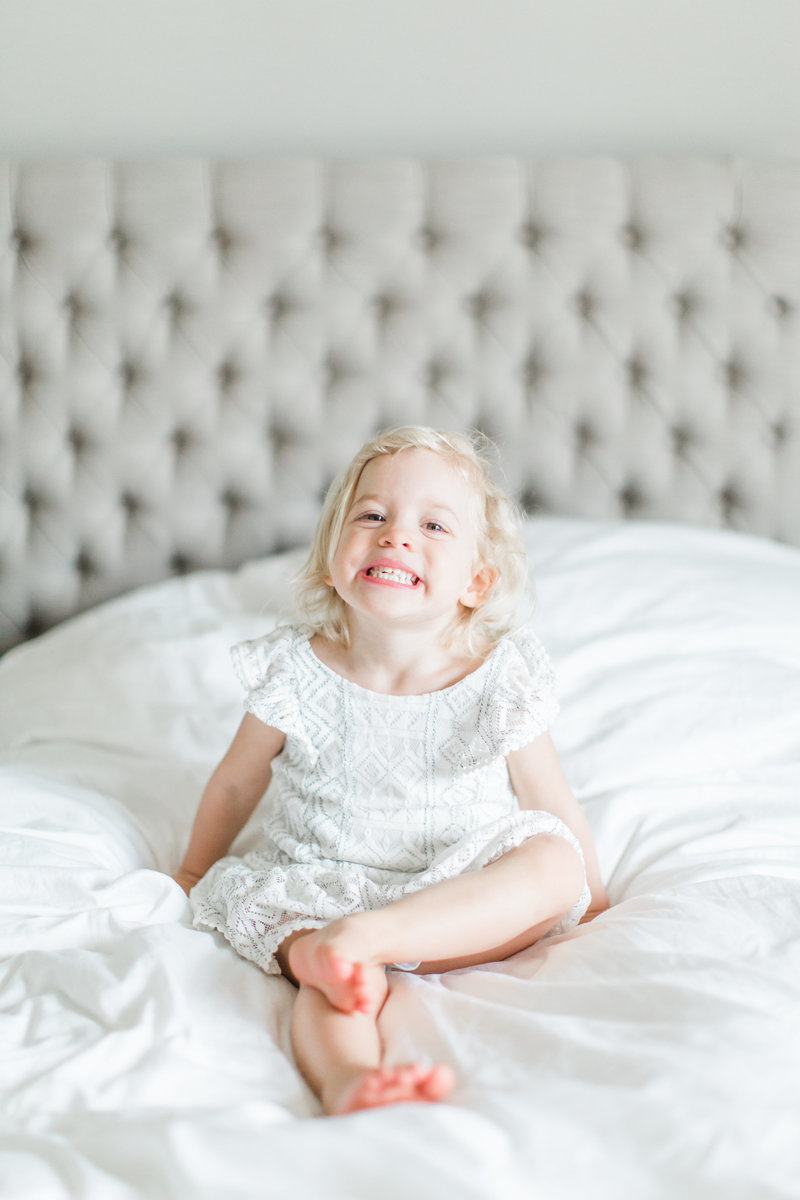 Little Girl Smiling on Bed Lifestyle Shoot