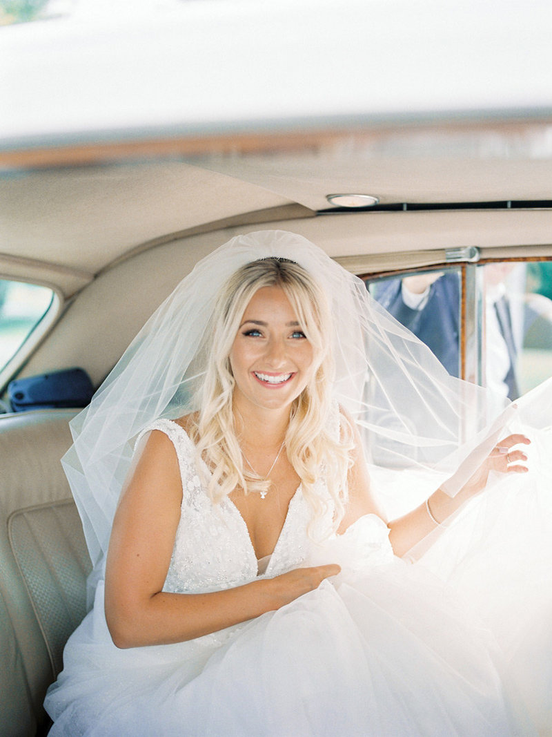 Bride riding in a white vintage car to church