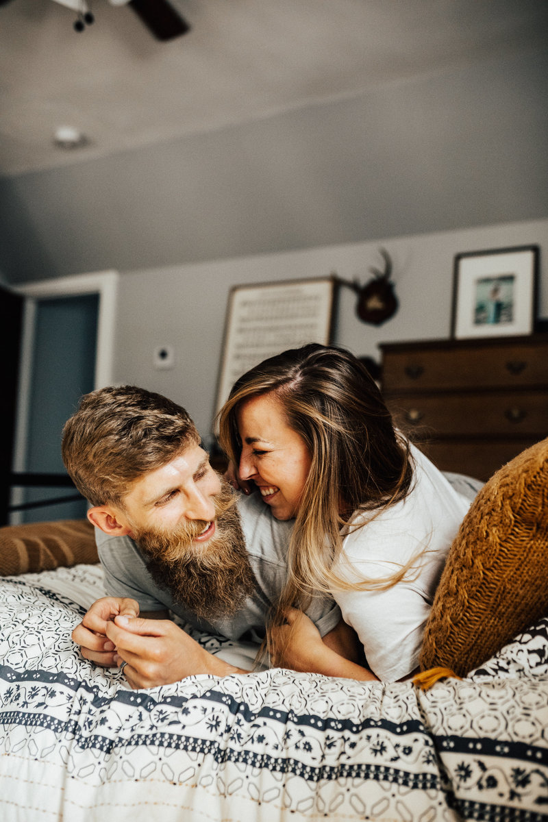 couple laughing on bed