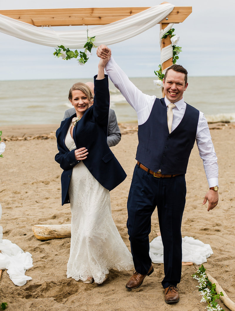 Bride and groom raise their hands after their Presque Isle beach wedding