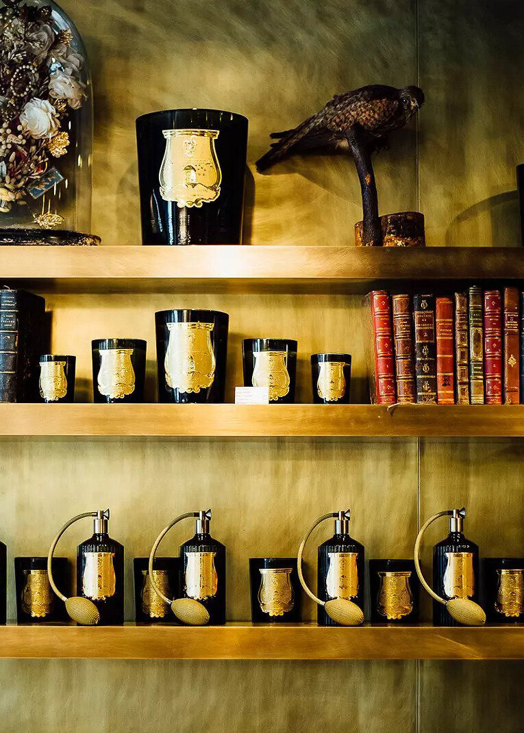 A selection of Cire Trudon candles sit on wooden shelves.