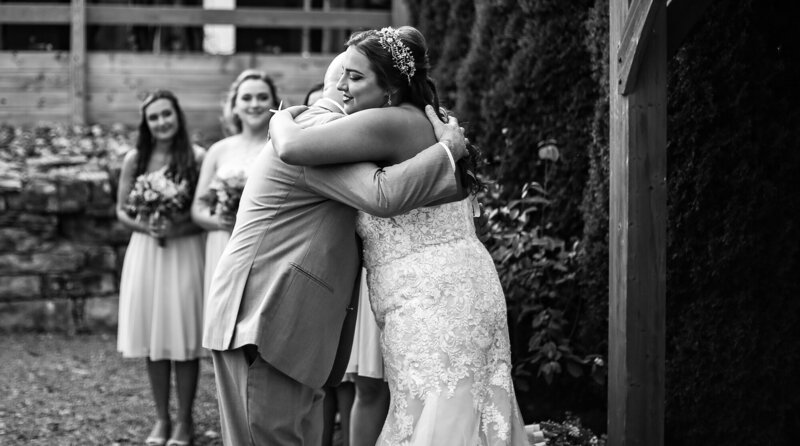 Bride hugs father as he gives her away during Port Farms wedding ceremony