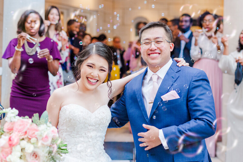 An Asian-American couple smile as they leave their wedding in a bubble exit at the Wimbish House in Atlanta Georgia.