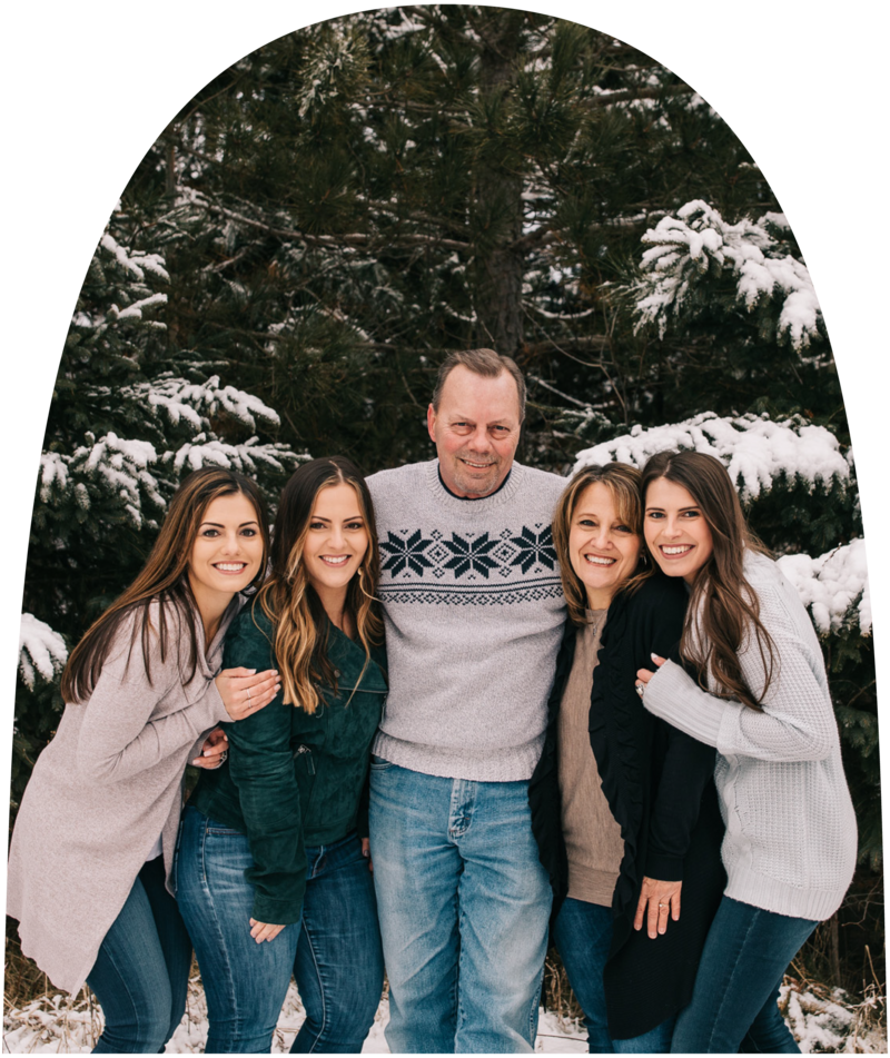Jenna with her mom, dad, and sisters embracing and smiling at the camera