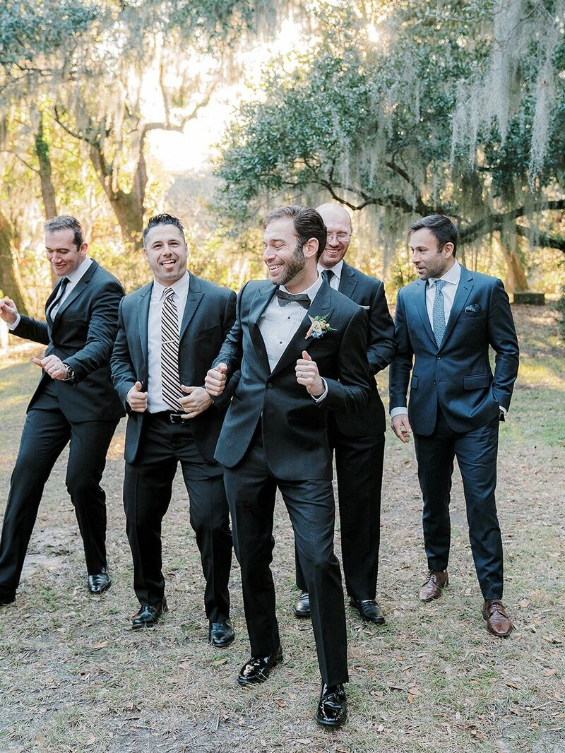 Groom with his wedding party dancing in their wedding suits