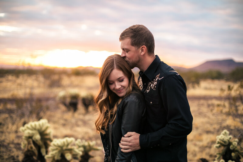 couples portrait in desert of man kissing woman on the head