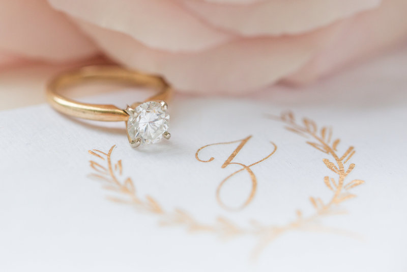 Detail shot of an engagement ring with calligraphy in gold ink